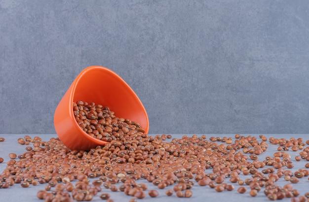Pomarańczowa miska umieszczona w kupie czerwonej fasoli na marmurowej powierzchni