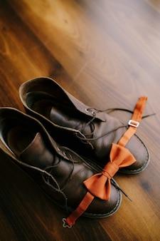 Pomarańczowa muszka dla pana młodego na brązowych męskich butach z niezawiązanymi sznurowadłami