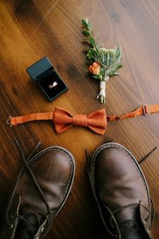 Pomarańczowa muszka dla pana młodego z pierścionkiem butonierki w pudełku i męskie buty na brązowej podłodze
