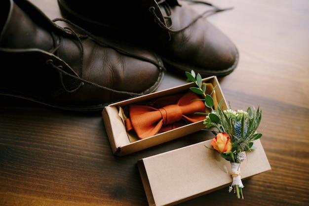 Pomarańczowa muszka w kartonowym pudełku dla pana młodego z pączkiem i męskimi butami