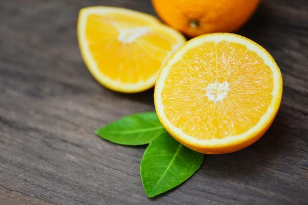 Pomarańczowa owoc na drewnianym tle - świeża pomarańczowa plasterek połówka i pomarańczowego liścia owoc żniwa zdrowy pojęcie