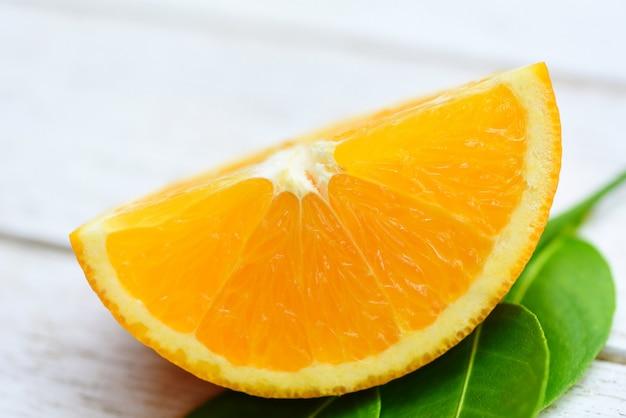 Pomarańczowa owoc na drewnianym tle / zamyka w górę świeżej pomarańczowej plasterek połówki i pomarańczowego liścia zdrowych owoc