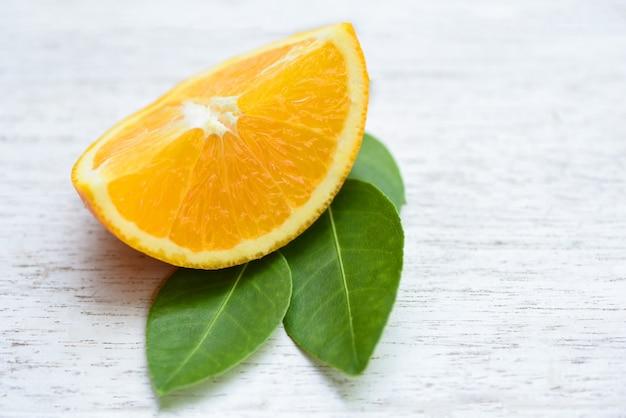 Pomarańczowa owoc - świeża pomarańczowa plasterek połówka i pomarańczowy liść zdrowych owoc pojęcie
