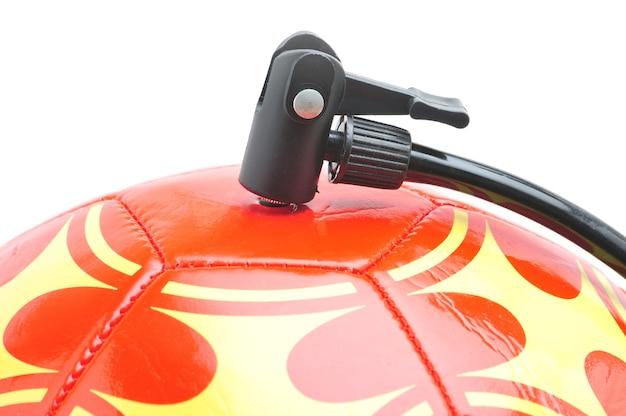 Pomarańczowa piłka nożna z pompką na na białym tle