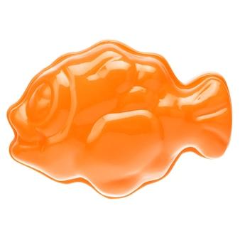 Pomarańczowa plastikowa ryba na białym tle, zbliżenie.