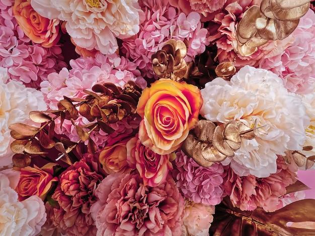 Pomarańczowa róża i inne różowe białe kwiaty zdobione