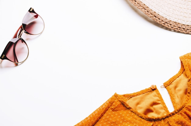 Pomarańczowa sukienka, słomkowy kapelusz i okulary na białym tle.
