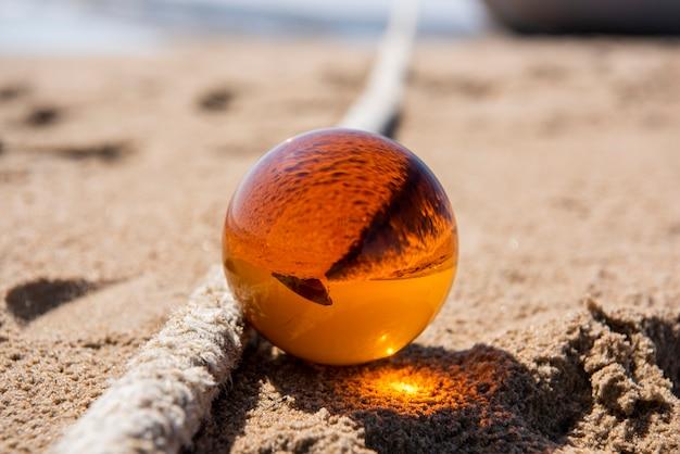 Pomarańczowa szklana kula na piasku w pobliżu morza