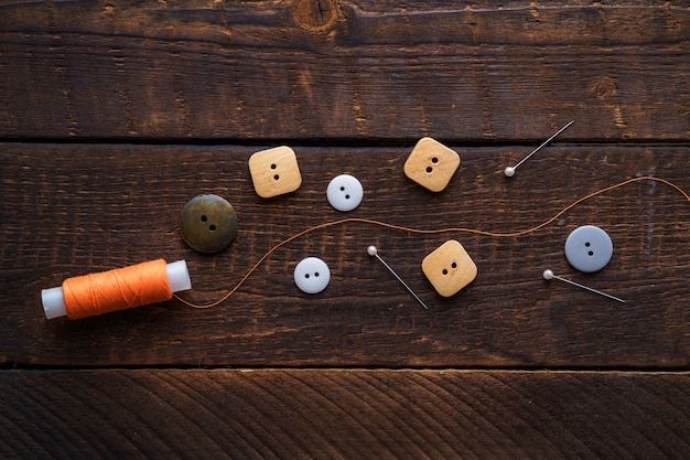 Pomarańczowa szpula nici, szpilki i guziki do szycia na drewnianej brązowej powierzchni