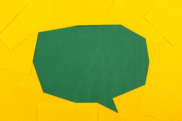 Pomarańczowe arkusze papieru leżą na zielonej tablicy szkolnej i tworzą bąbelek czatu z miejscem na kopię tekstu.