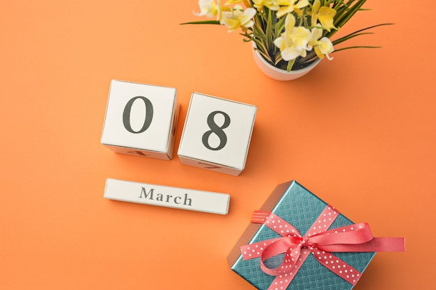 Pomarańczowe biurko z prezentem, kwiatami i notatnikiem