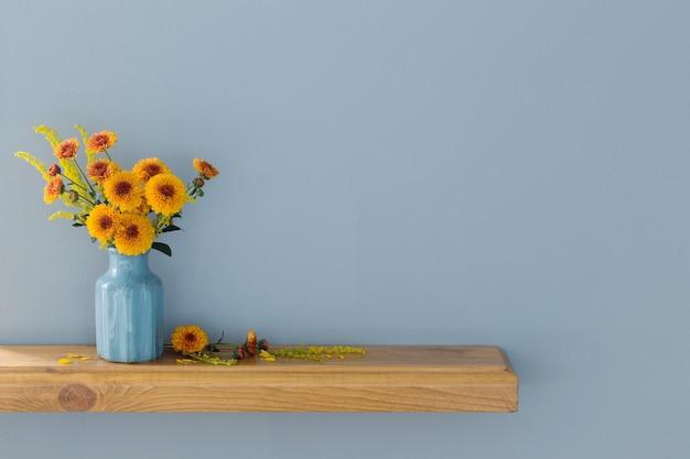 Pomarańczowe chryzantemy w niebieskim wazonie na drewnianej półce na ścianie w tle