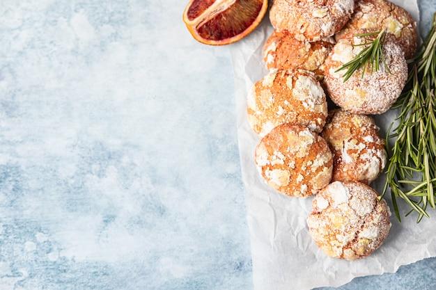 Pomarańczowe ciasteczka marszczone z cukrem pudrem na papierze do pieczenia