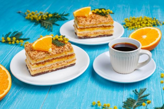 Pomarańczowe ciasto ozdobione świeżymi pomarańczowymi plasterkami i kwiatami mimozy na świetle