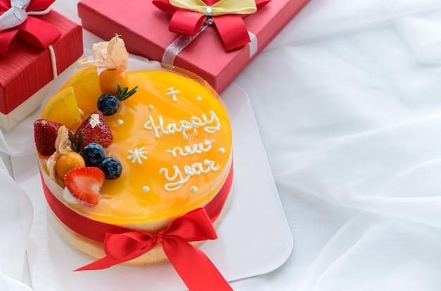 Pomarańczowe ciasto z szczęśliwego nowego roku z pomarańczą, truskawką, jagodami i cape agrest na białym obrusie, kopia przestrzeń i koncepcja deseru