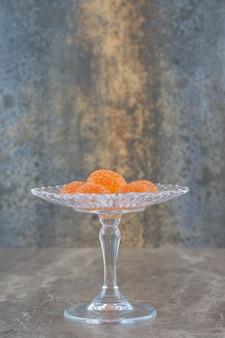 Pomarańczowe cukierki galaretki nad cukiernicą na szarej ścianie. zdjęcie pionowe.