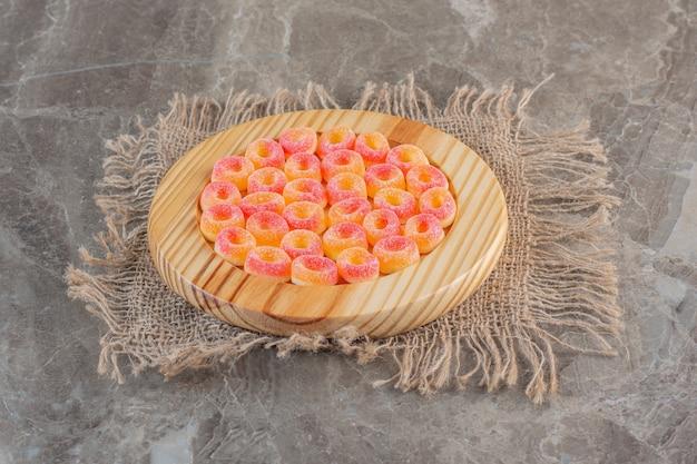Pomarańczowe cukierki galaretki w kształcie pierścienia na drewnianej płycie.