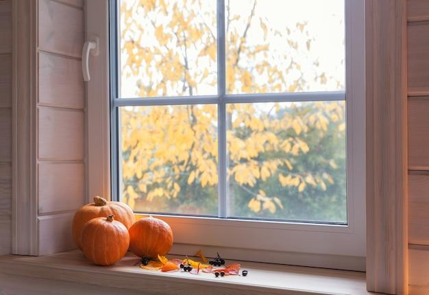 Pomarańczowe dynie na parapecie, świece, jesienne liście, latarnia.