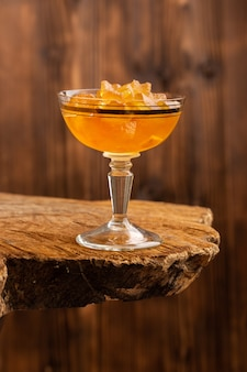 Pomarańczowe galaretki wewnątrz szkła na brązowym drewnie