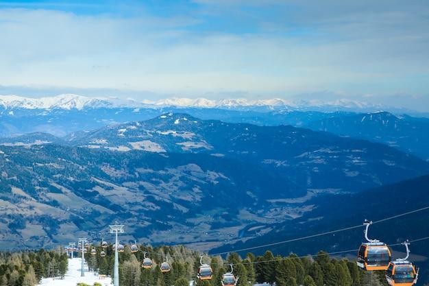 Pomarańczowe gondoli kabiny cableway dźwignięcie na zim gór śnieżnym tle pięknej scenerii