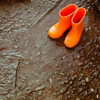 Pomarańczowe gumowe buty stojące obok kałuży.