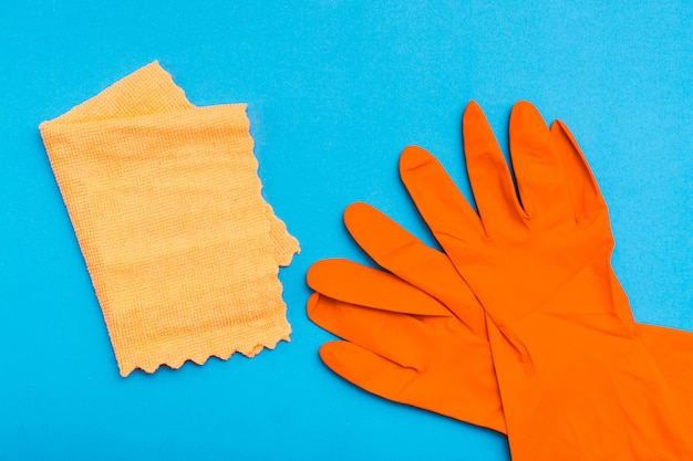 Pomarańczowe gumowe rękawiczki i żółta szmata z mikrofibry na niebieskim tle
