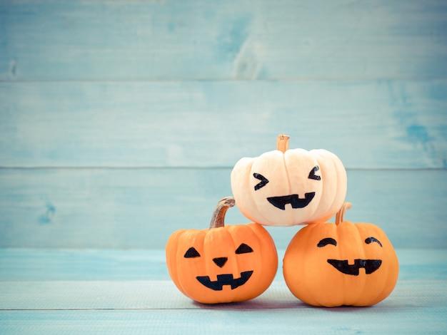 Pomarańczowe i białe banie halloween dekorują na błękitnym drewnianym tle.