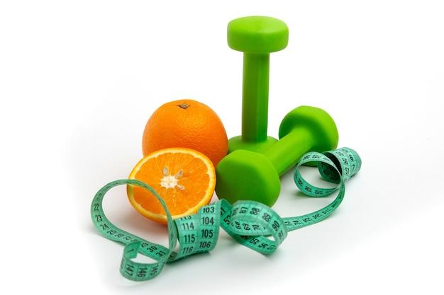 Pomarańczowe i zielone hantle z miarką na białym tle