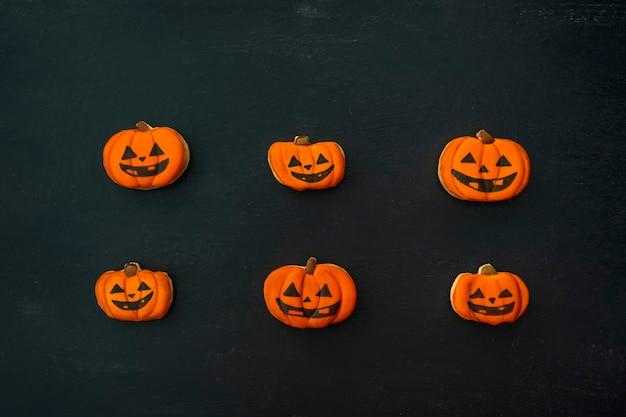 Pomarańczowe imbirowe ciasteczka na halloween w formie dyni leżą poziomo na ciemnym stole. uśmiechnięty plik cookie. widok z góry na stole.