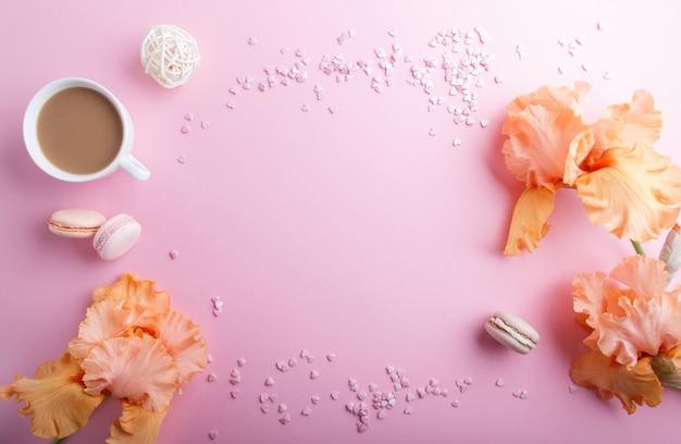 Pomarańczowe irysowe kwiaty i filiżanka kawy na różowym pastelowym tle.