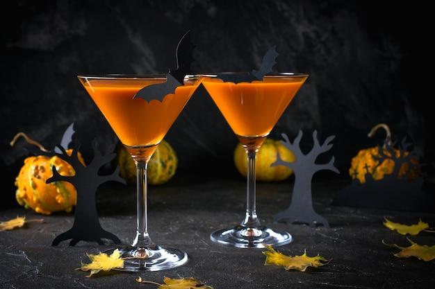 Pomarańczowe koktajle martini z nietoperzami i wystrojem na imprezę halloween, na ciemnym tle