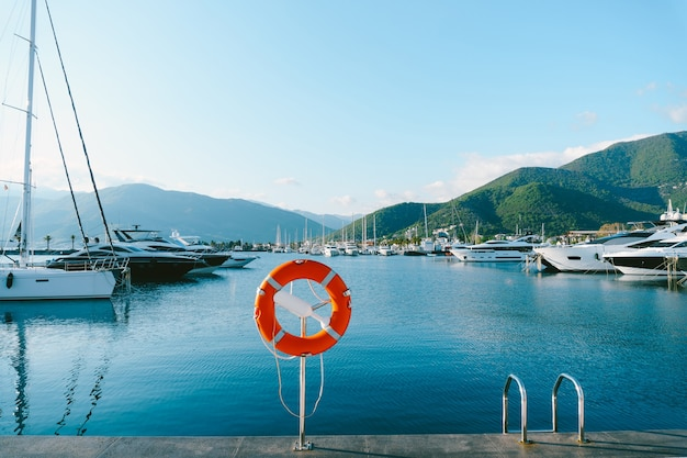 Pomarańczowe koło ratunkowe na chromowanej podstawie, na przystani w porto montenegro, elitarnym obszarze czarnogóry, mieście tivat