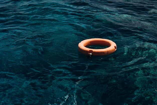 Pomarańczowe koło ratunkowe na niebieskim morzu