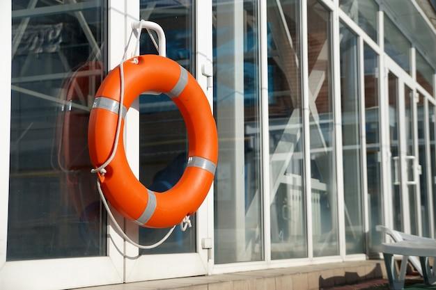 Pomarańczowe koło ratunkowe na ścianie osłony basenu