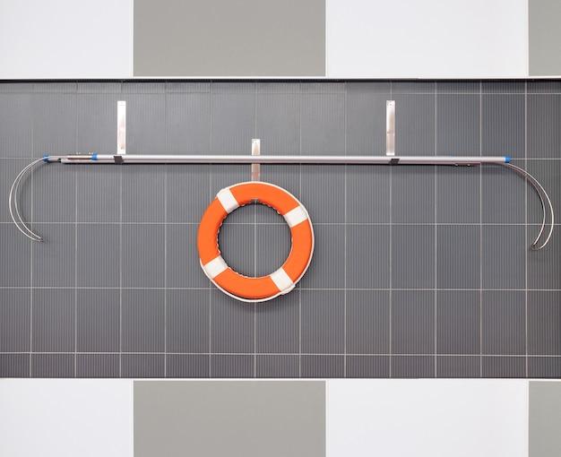 Pomarańczowe koło ratunkowe wiszące na ścianie w basenie
