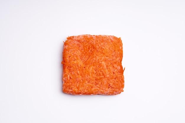 Pomarańczowe kostki mrożonej startej marchwi. zakup mrożonek. półprodukt.