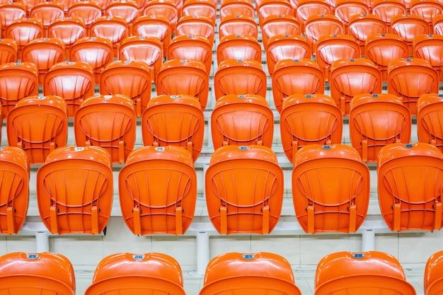 Pomarańczowe krzesła stoją w rzędzie na krytym stadionie. tribune dla fanów