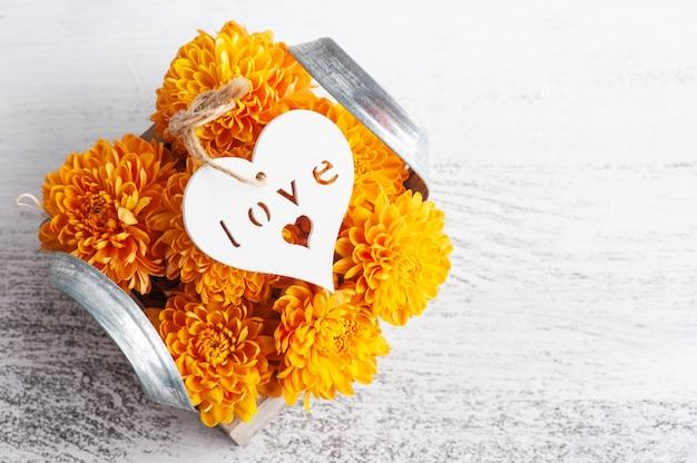 Pomarańczowe kwiaty w pudełku na rustykalnym stole. kartkę z życzeniami z sercem