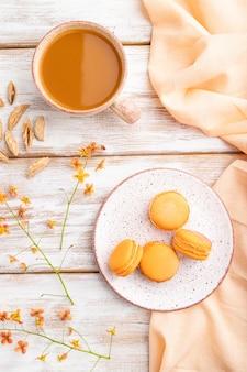 Pomarańczowe macarons lub ciasta makaronikowe z filiżanką soku morelowego na białym drewnianym