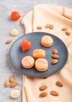 Pomarańczowe macarons lub ciastka macaroons na niebieskim talerzu ceramicznym. widok z boku.