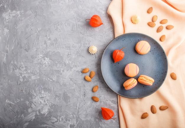 Pomarańczowe macarons lub ciastka macaroons na niebieskim talerzu ceramicznym. widok z góry.