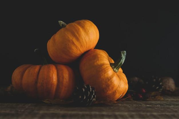 Pomarańczowe małe dynie na ciemnym drewnie