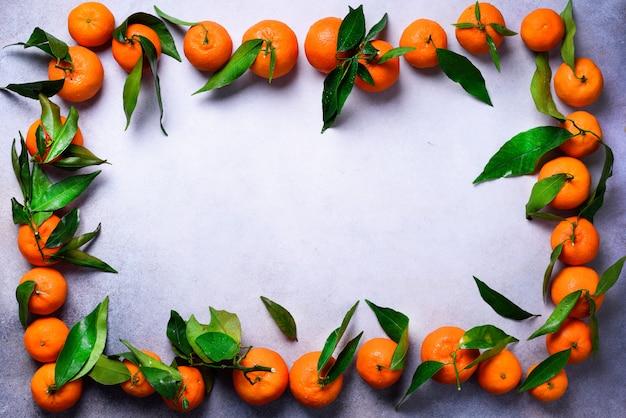 Pomarańczowe mandarynki (pomarańcze, mandarynki, klementynki, owoce cytrusowe) z zielonymi liśćmi na jasnym tle, kopia przestrzeń
