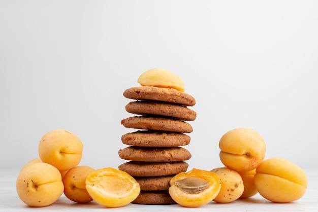 Pomarańczowe morele z widokiem z przodu, przyprawione ciasteczkami na jasnym biurku
