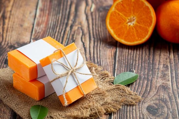 Pomarańczowe mydło ze świeżą pomarańczą na ciemnym drewnianym tle