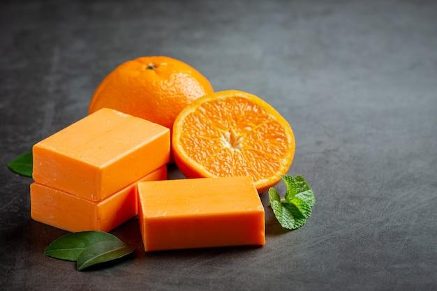 Pomarańczowe mydło ze świeżą pomarańczą na ciemnym tle
