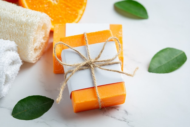 Pomarańczowe mydło ze świeżą pomarańczą na marmurowym tle