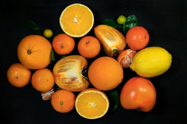 Pomarańczowe owoce z liśćmi na czarnym tle