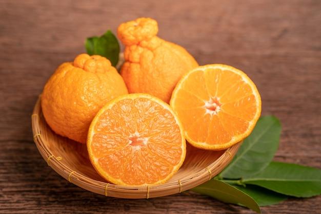 Pomarańczowe owoce z plastrami pomarańczy i liśćmi w koszyku dekopon mandarynka lub mandarynka sumo z liśćmi w koszyku