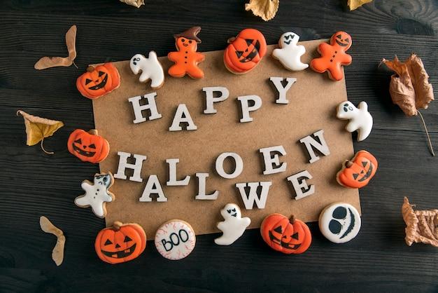 Pomarańczowe pierniki i napis happy halloween na czarnym drewnianym stole. pocztówka happy halloween słodkie tło